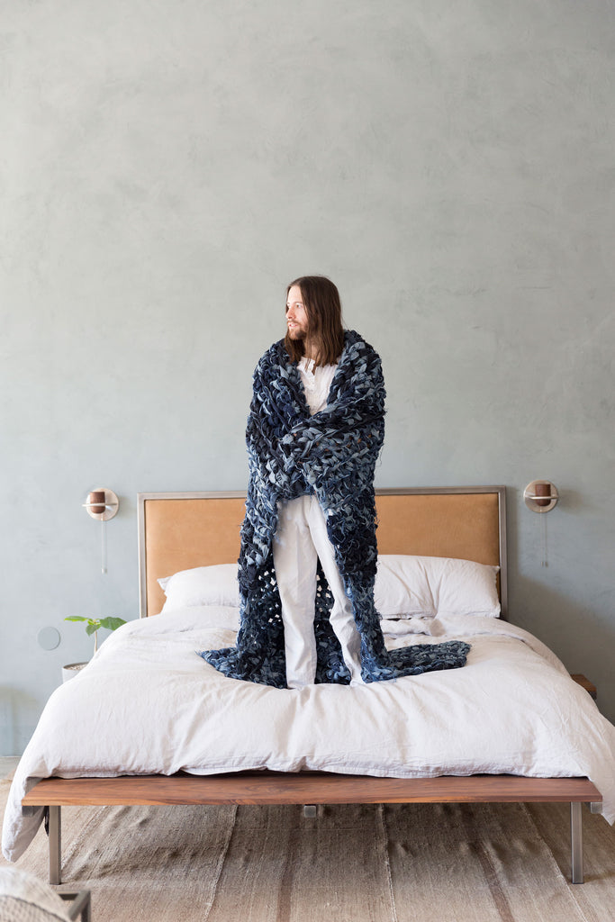 man standing on bed with denim weighted blanket over shoulders