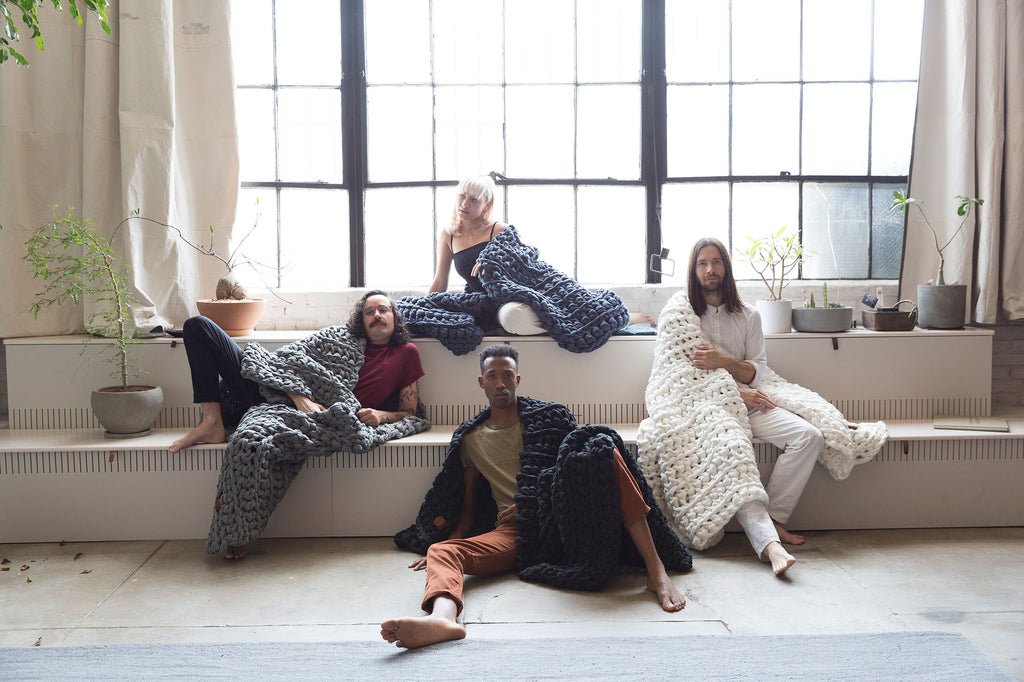 four people modeling weighted blankets in studio