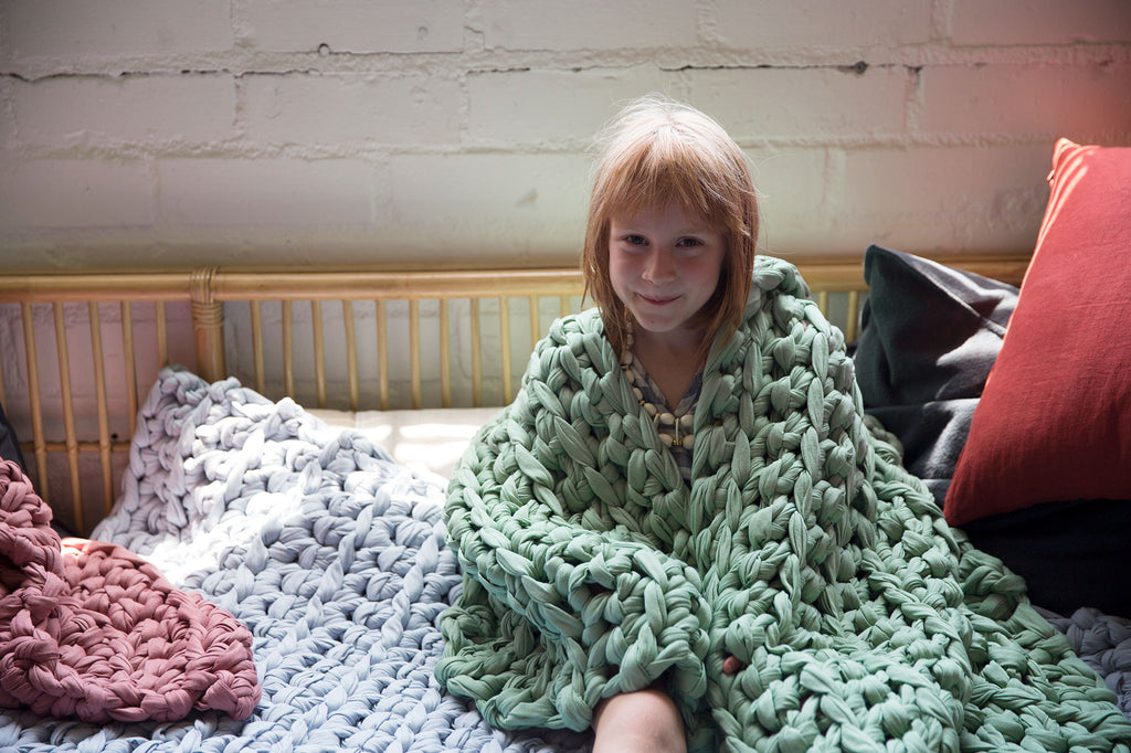 girl with sea glass weighted blanket draped over shoulders