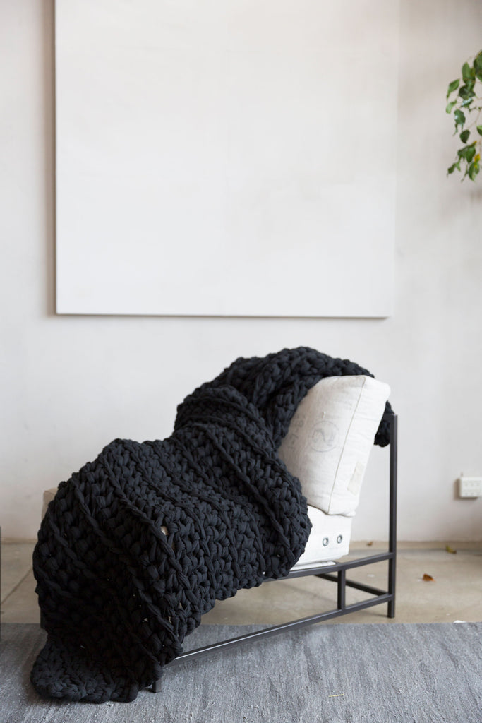 vintage noir black weighted blanket draped over chair