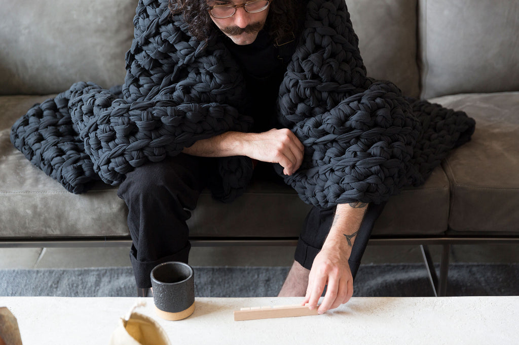 man with vintage noir black weighted blanket over shoulders