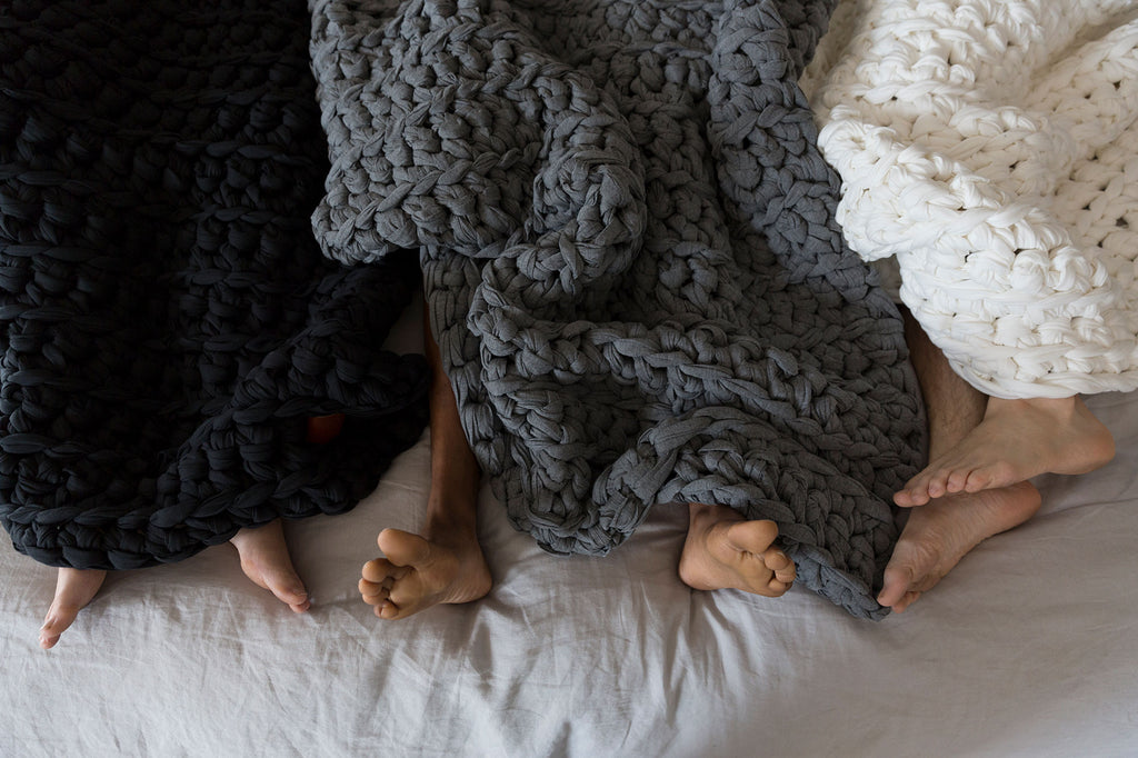 three pairs of feet underneath weighted blankets