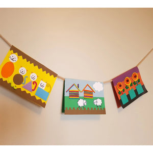 three hand made picture cards hang in a rope