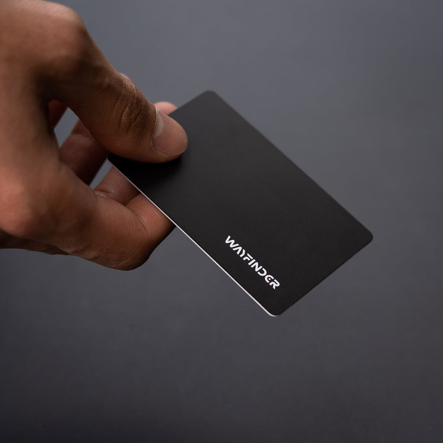 GLITCH RFID Data Blocking Card held in hand on dark gray background