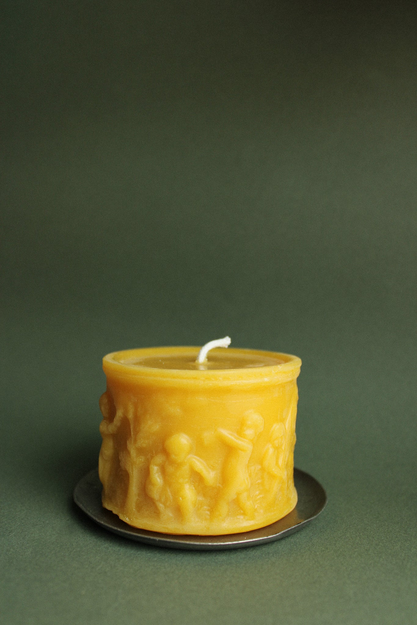 100% beeswax pillar candle in front of a forest green backdrop. The candle features a scene of angelic children gardening.