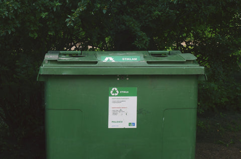 green recycling bin in front of trees