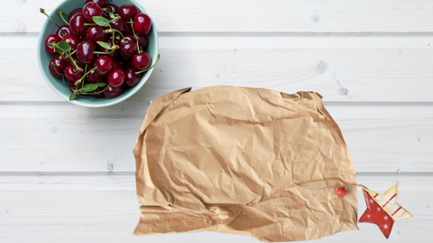 kraft brown packing paper on a white wooden table with a bowl of cherries