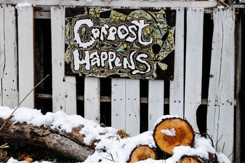 """compost happens"" sign on a fence hanging above tree logs covered in snow"