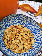 Toasted pumpkin seeds in blue coloured coconut bowl