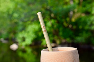 Upclose picture of bamboo straw with three tree logo in bamboo cup