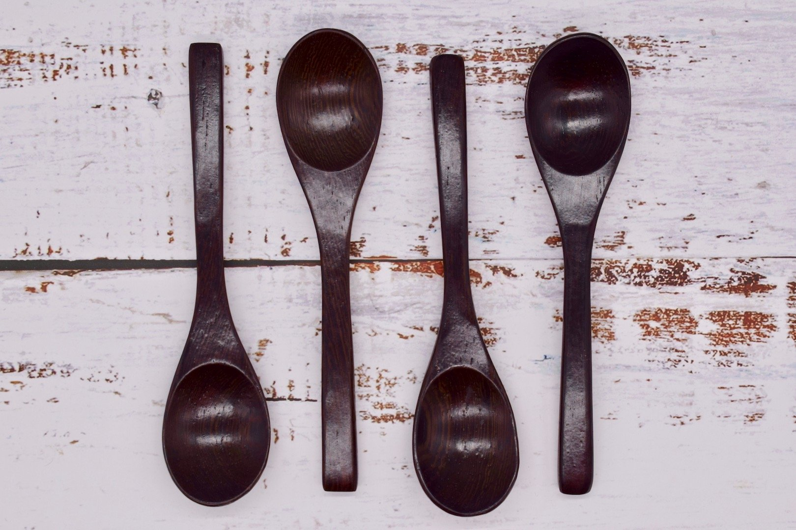 4 Ebony spoons laid out top to tail