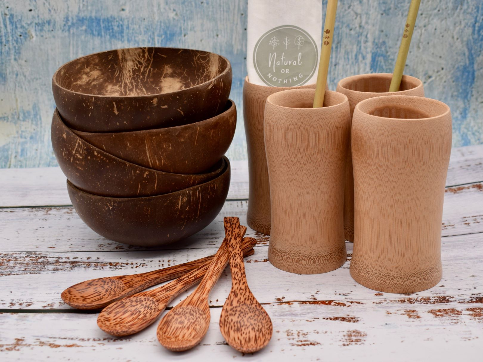 Ultimate kitchen set includes picture: 4 natural coconut bowls, 4 bamboo cups, pack of 10 bamboo straws with bag and cleaner, 4 wood spoons
