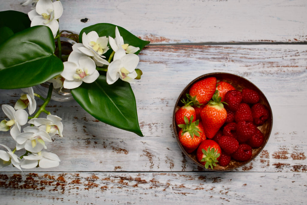 Natural coconut bowl on table filled with fresh summer fruits