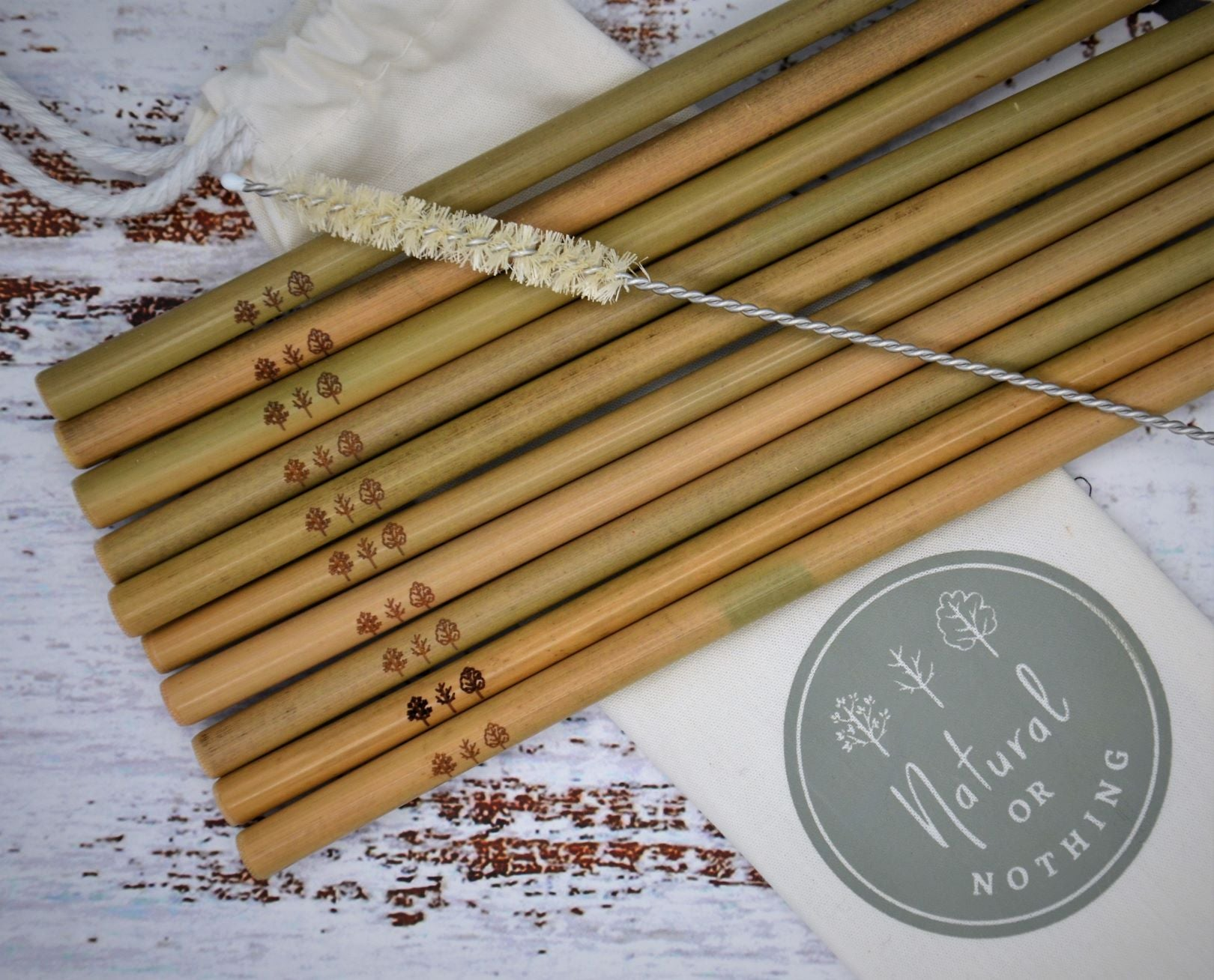 Bamboo straws up close, laid over canvas bag with sisal straw cleaner laid on top