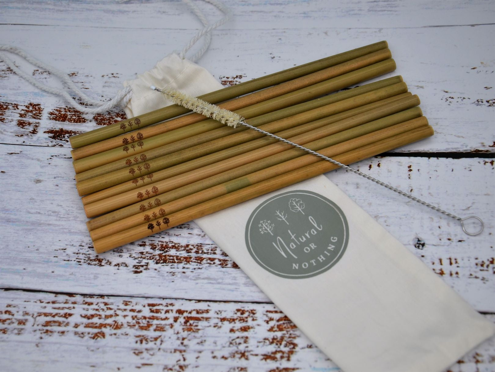 10 Bamboo straws laid over drawstring bag with sisal straw cleaner