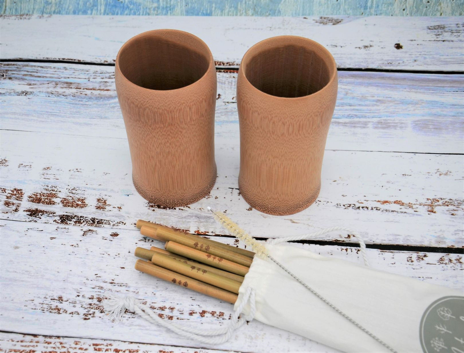 Bamboo cups and straws in canvas bag with sisal cleaner laid on top of bag