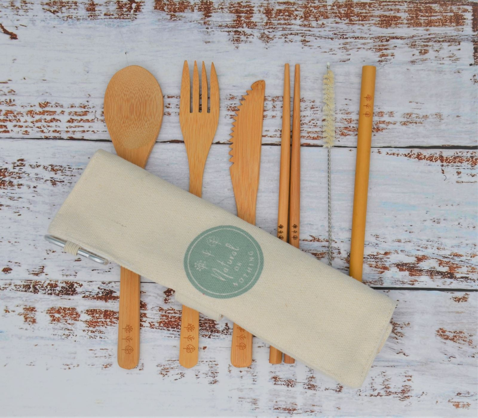 Bamboo cultery set with canvas travel cutlery bag laid over cutlery
