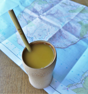 Bamboo straw in use with bamboo cup, sitting on a map