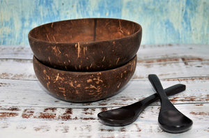 Two Jumbo Coconut Bowls stacked with two ebony wood spoons laid beside bowls