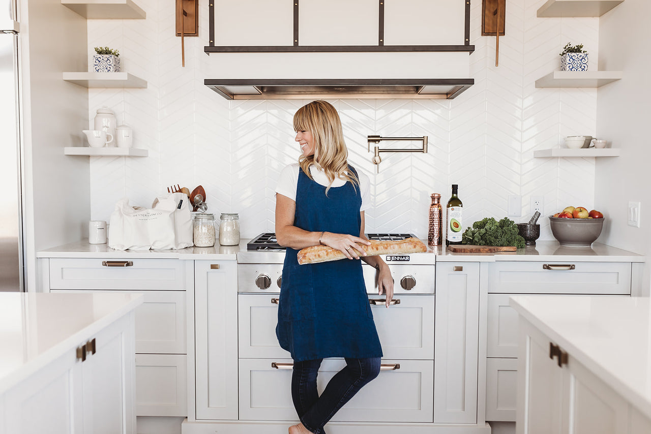 A woman standing in the kitchen wearing a navy blue linen apron. Pinafore style with cross back