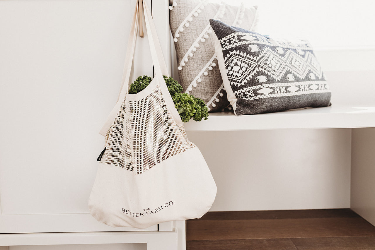 A perfect blend tote hanging on the door after shopping at the farmers market. Made with a mesh top and canvas bottom