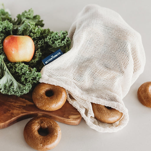 The Better Farm Co's three Mesh Produce Bags sit on a countertop, filled with produce and surrounded by other sustainable, zero-waste goods. The cotton mesh produce bags are organic, and have uses beyond gathering produce at the grocery store. They are the perfect plastic-free alternative, and are versatile. You can use them for produce, lunch bags, washing bags, organizing suitcases or storing baby items in your bag.