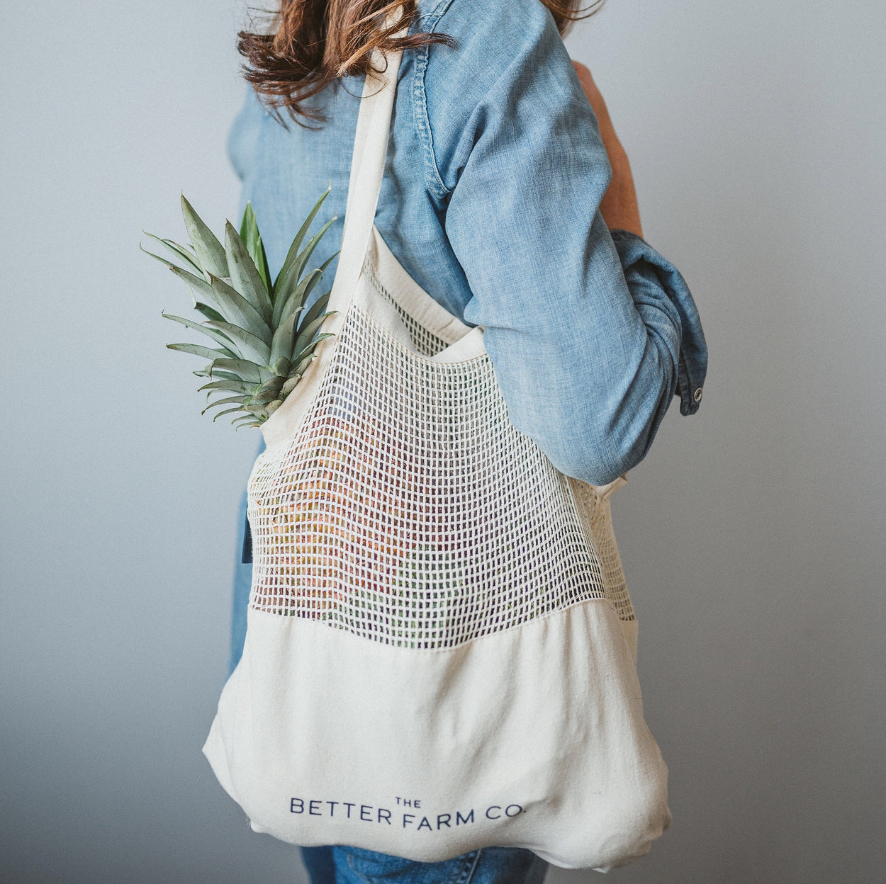 The Better Farm Co's Perfect Blend Bag is shown slung over a woman's shoulder, holding various bulk and produce items. The organic, sturdy canvas bottom keeps your groceries tucked away where they should be, without tops poking out of your string bag. This bag is pretty, practical, and eco friendly-your new grocery store companion.