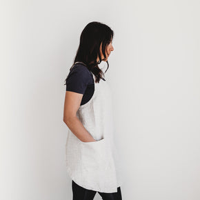 The Better Farm Co's French Linen Apron in the color Wheat is worn by a dark haired woman, turned towards the side. The French Linen Apron has a crossback design, inspired by French and Japanese style. This sustainable and eco-friendly design has no fuss with ties, and is pretty yet functional. It is perfect for the studio, grocery store, kitchen, or just worn over top of jeans.