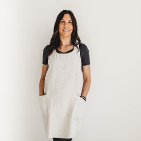 The Better Farm Co's French Linen Apron in the color Wheat is worn by a dark haired woman, staring straight at the camera. The French Linen Apron has a crossback design, inspired by French and Japanese style. This sustainable and eco-friendly design has no fuss with ties, and is pretty yet functional. It is perfect for the studio, grocery store, kitchen, or just worn over top of jeans.