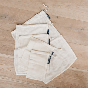The Better Farm Co's five Mesh Produce Bags are laid flat on a light hardwood surface. The cotton mesh produce bags are organic, and have uses beyond gathering produce at the grocery store. They are the perfect plastic-free alternative, and are versatile. You can use them for produce, lunch bags, washing bags, organizing suitcases or storing baby items in your bag.