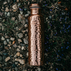 The Better Farm Co's sustinable copper water bottle is placed on top of grass and rocks outside, the perfect water bottle for an eco-friendly grocery run. Copper has many benefits. including  ayurvedic healing, increasing immunity, aiding in gut health, increasing metabolism, providing arthritic support and improving digestion.