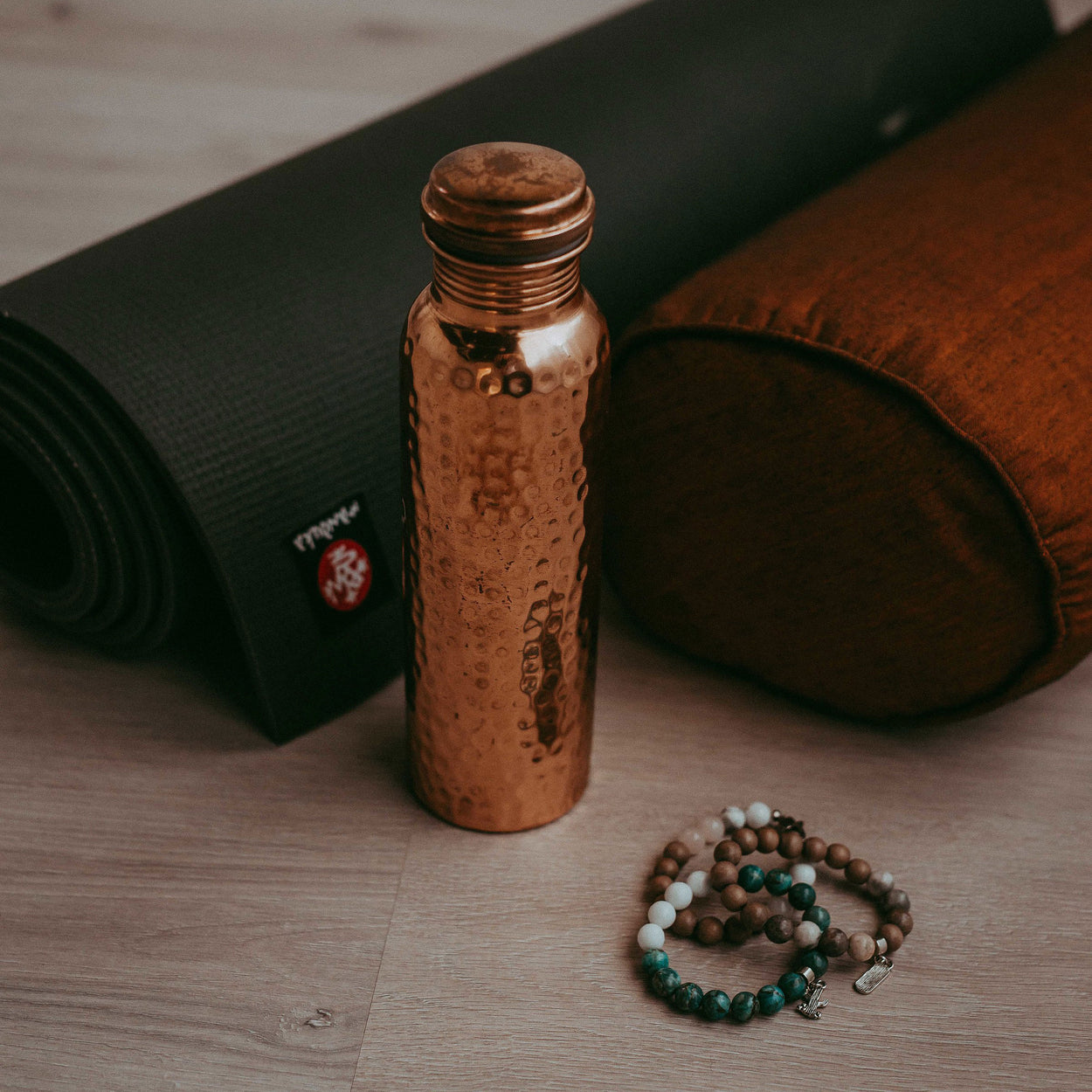 The Better Farm Co's sustinable copper water bottle rests near a yoga mat and bracelets on the floor, the perfect water bottle for an eco-friendly grocery run. Copper has many benefits. including  ayurvedic healing, increasing immunity, aiding in gut health, increasing metabolism, providing arthritic support and improving digestion.