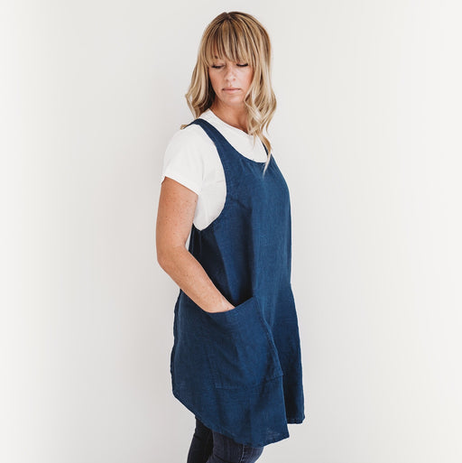 The Better Farm Co's French Linen Apron in the color Pacific is worn by a blond woman, looking over her shoulder. The French Linen Apron has a crossback design, inspired by French and Japanese style. This sustainable and eco-friendly design has no fuss with ties, and is pretty yet functional. It is perfect for the studio, grocery store, kitchen, or just worn over top of jeans.