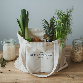 The Better Farm Co's Farm Tote is shown sitting upright on light hardwood, filled with produce and various bulk items. The organic canvas Farm Tote is the perfect sustainable companion for the farmers market or grocery store. It is made of certified organic cotton, and is eco-friendly and reusable. The size is perfect for shopping, as each one carries nearly three times your average grocery bag.