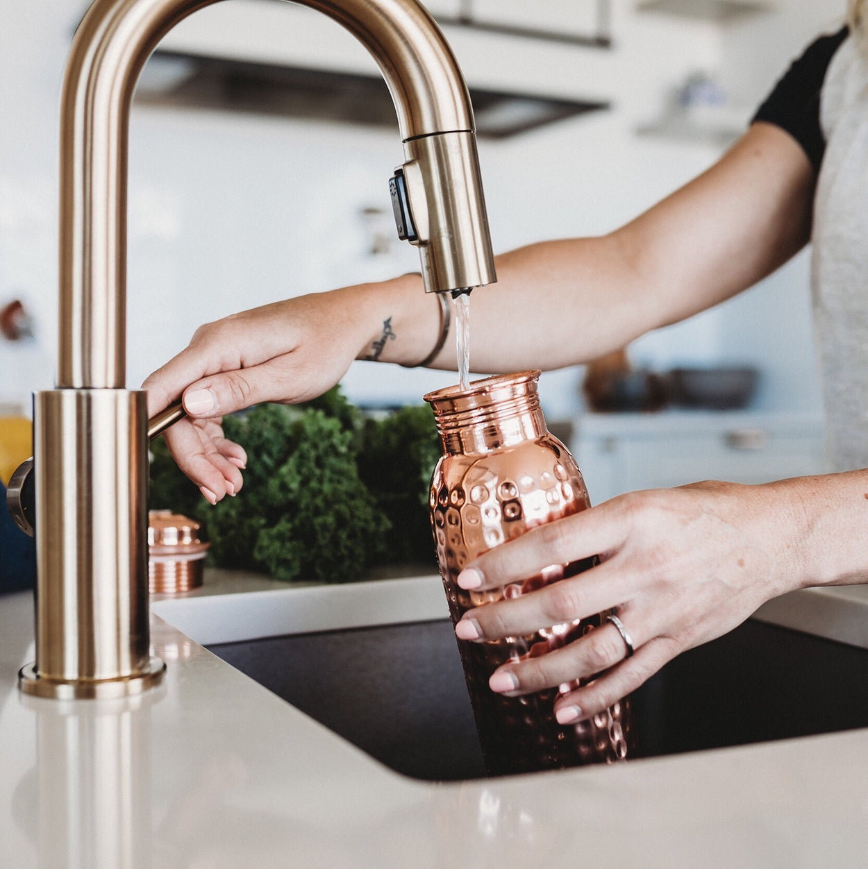 The Better Farm Co's sustinable copper water bottle is held under a kitchen sink nozzle, the perfect water bottle for an eco-friendly grocery run. Copper has many benefits. including  ayurvedic healing, increasing immunity, aiding in gut health, increasing metabolism, providing arthritic support and improving digestion.