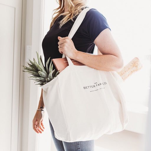 The Better Farm Co's organic canvas Farm Tote is slung over the shoulder of a woman standing near a doorway. The organic canvas Farm Tote is the perfect sustainable companion for the farmers market or grocery store. It is made of certified organic cotton, and is eco-friendly and reusable. The size is perfect for shopping, as each one carries nearly three times your average grocery bag.