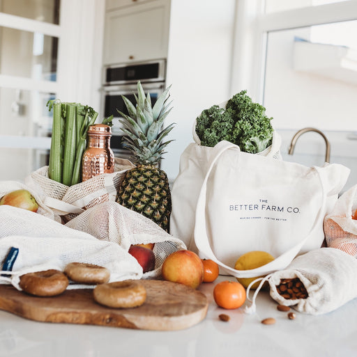 The Better Farm Co's Organic Cotton Shopping Set is shown sitting on top of a counter, bags filled with produce, surrounded by various zero-waste and sustainable goods. The organic cotton shopping set is your starting point for sustainable, eco-friendly shopping alternatives. Featuring organic cotton shopping bags, market bags, totes, and produce bags, you'll be set for your next market trip or grocery run. These bags are foldable and made to keep your shopping organized.