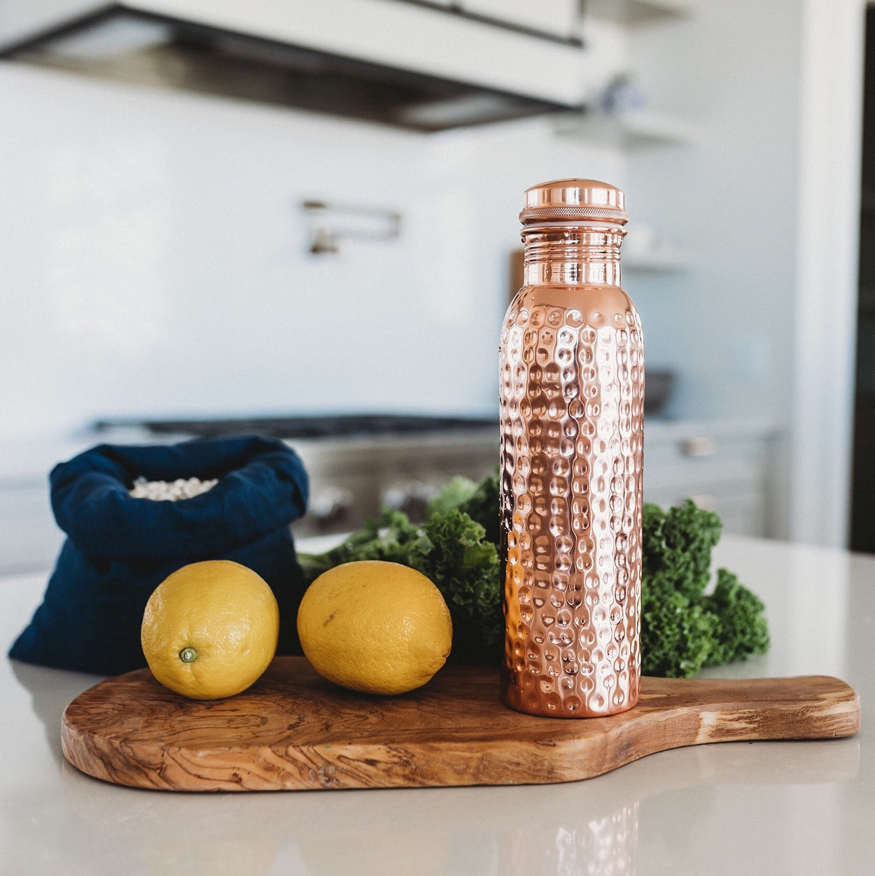 The Better Farm Co's sustinable copper water bottle is placed on top of a counter, the perfect water bottle for an eco-friendly grocery run. Copper has many benefits. including  ayurvedic healing, increasing immunity, aiding in gut health, increasing metabolism, providing arthritic support and improving digestion.