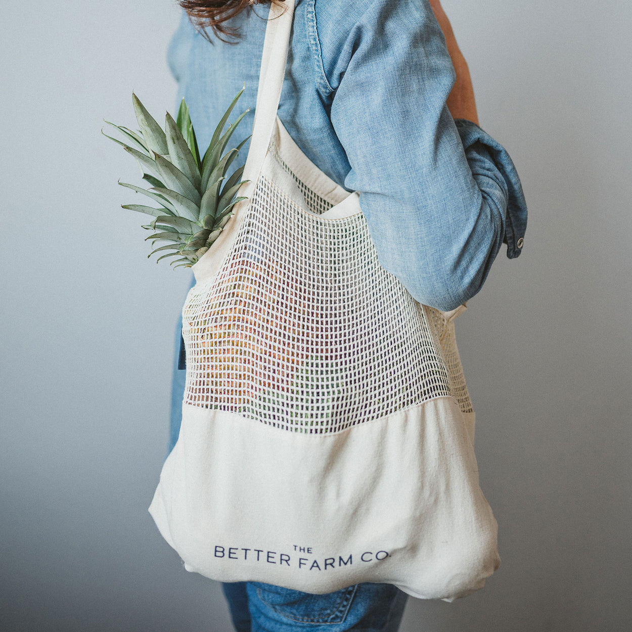 The Better Farm Co's Perfect Blend Bags are shown slung over a woman's shoulder, with produce and bulk goods held inside. The organic, sturdy, zero-waste and reusable canvas bottom keeps your groceries tucked away where they should be, without tops poking out of your string bag. This bag is pretty, practical, and eco friendly-your new sustainable grocery store companion.
