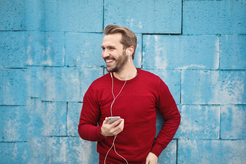 Man Holding Phone with Headphones Smiling - KryptoKratom.com
