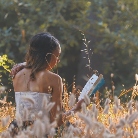girl sitting in summer field reading book