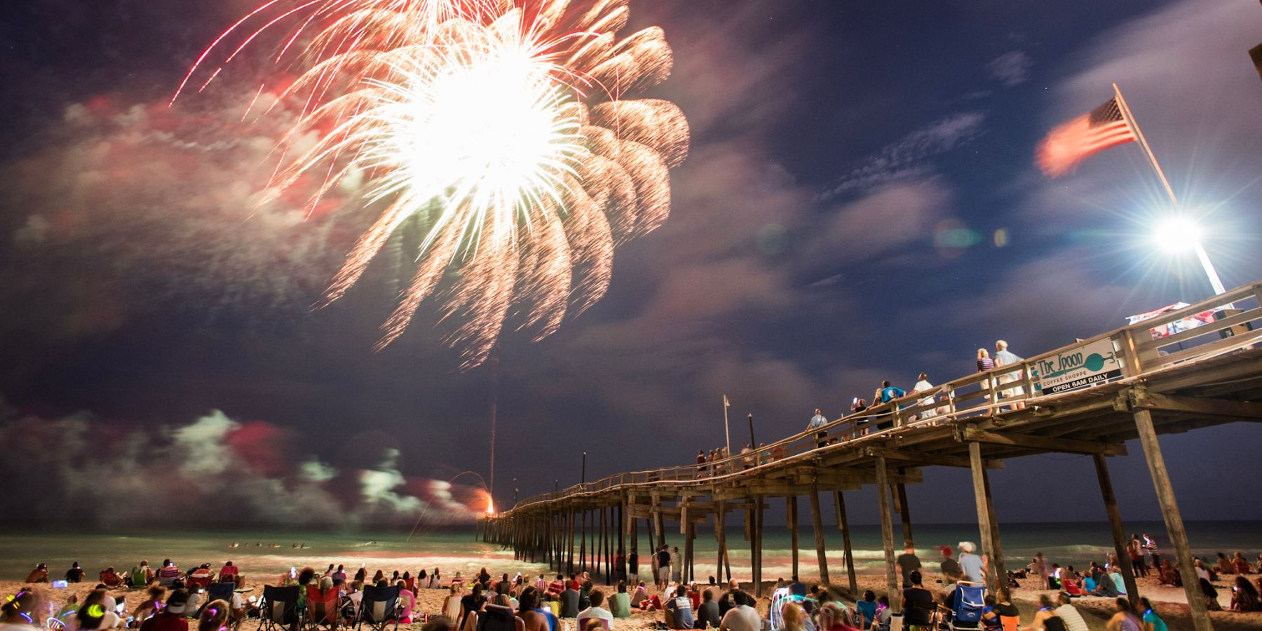 Fireworks are bursting over the Avon Pier while the crowd gathers below to watch. The American Flag is flying high above while the fireworks light up the sky on the 4th of July.