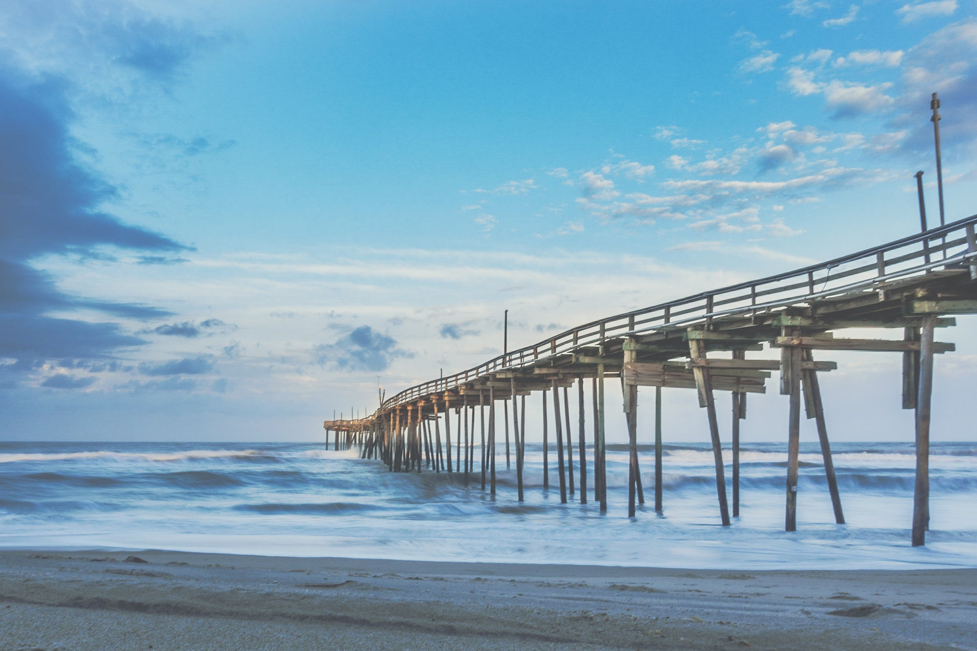The Avon Fishing Pier during a blue clear sunrise with beautiful clouds and the mystic Atlantic Ocean.