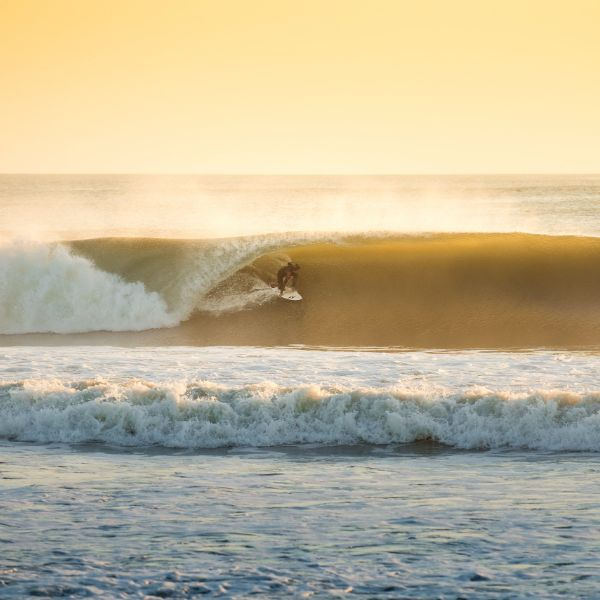 An Outer Bank's surfer enjoying the waves of Avon North Carolina during sunset's golden hour.