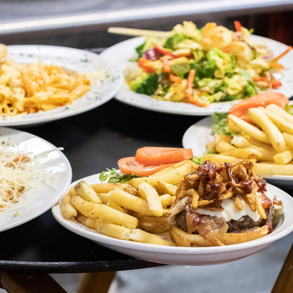 Plates of food including Pangea Tavern's famous burgers and Thai coconut curry on a tray ready for dinner service.