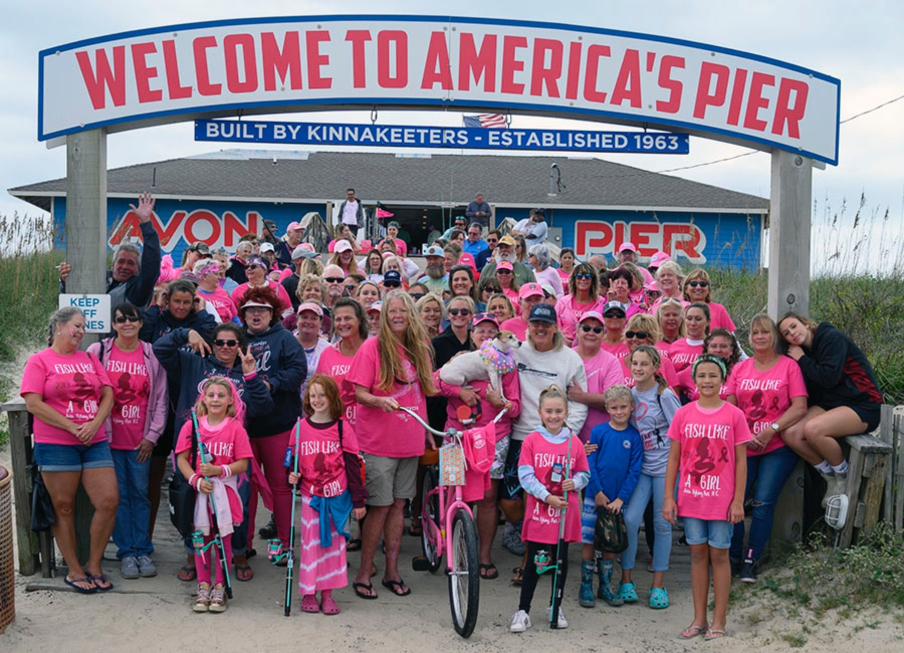 A group of women and girls in pink clothing celebrating the Fish Like A Girl all-ladies charity fishing tournament at the Avon Fishing Pier.