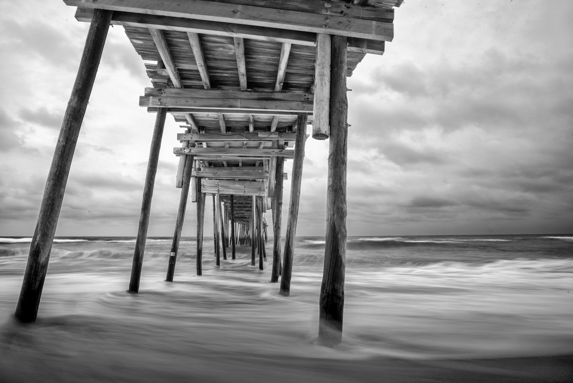 The Avon Fishing Pier in black and white with the waves of the Atlantic Ocean breaking on the Avon beach on the Outer Banks.
