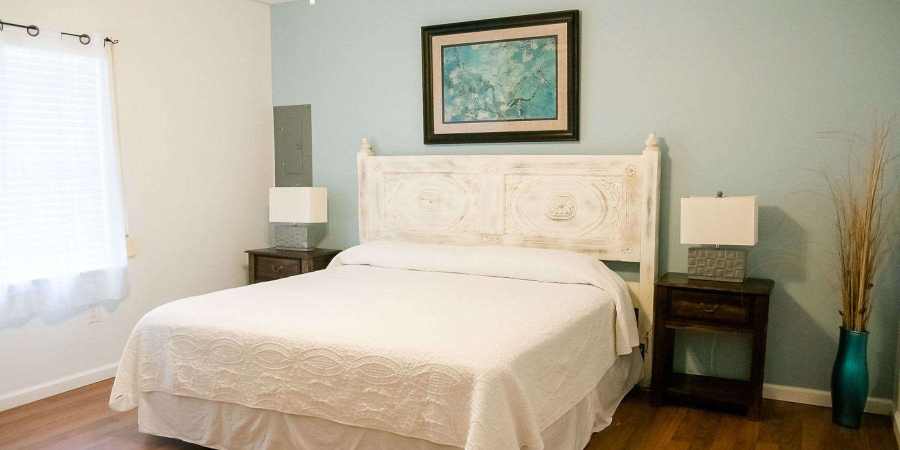 A bed in one of the Villas at Koru Village's accommodations. The room is decorated with light blue, teal, and white, while the Cape Hatteras sun shines in through the window.