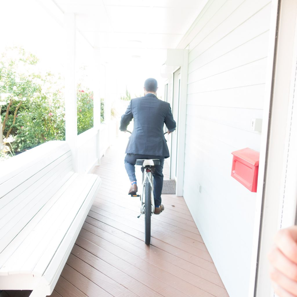 A man riding a beach cruiser bike through the Villa's at Koru Village walkway.