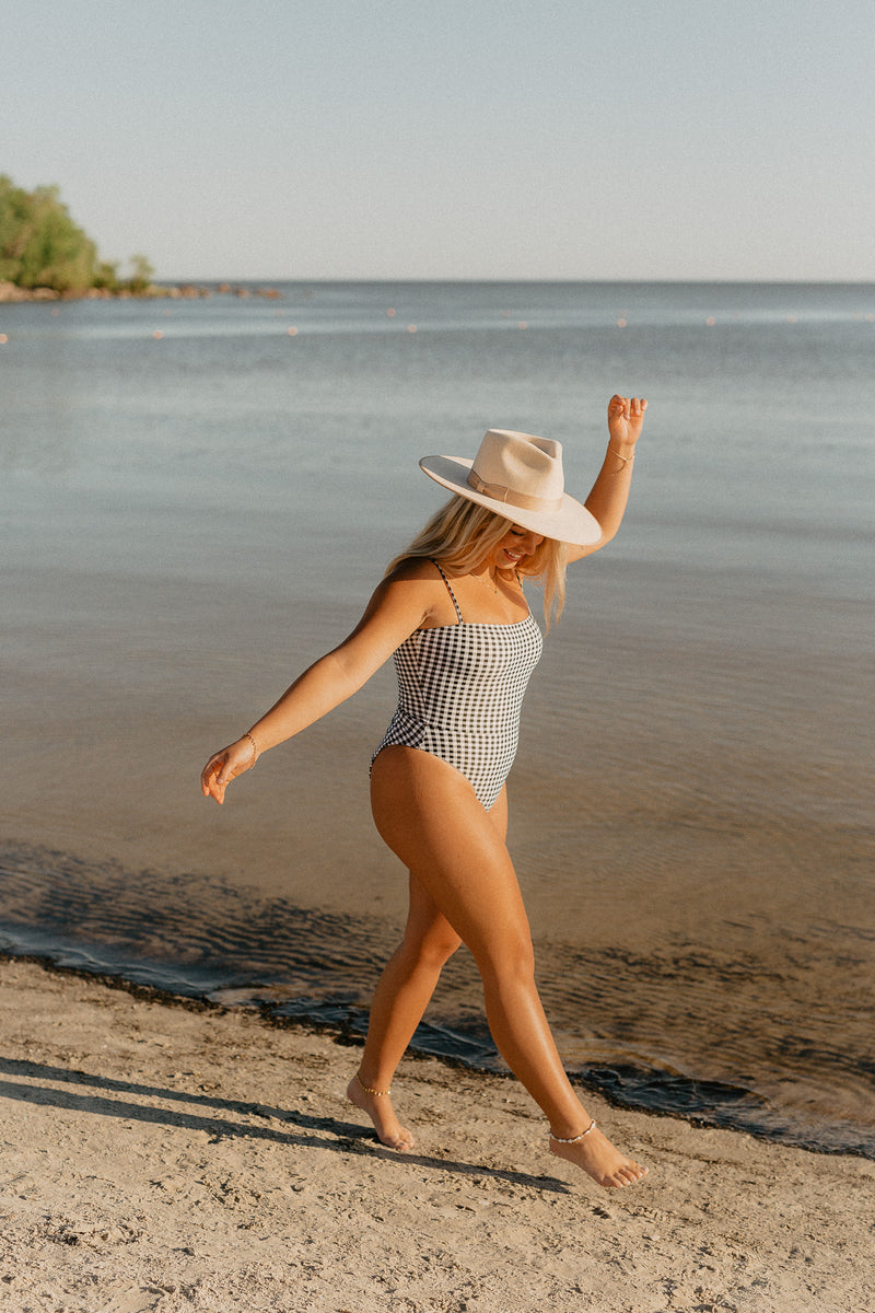 Influencer Nicole Zajac wears North American swimwear brand Prairie Swim chic straight neckline black and white gingham check print one piece swimsuit with adjustable straps, cinched waist and high cut legs